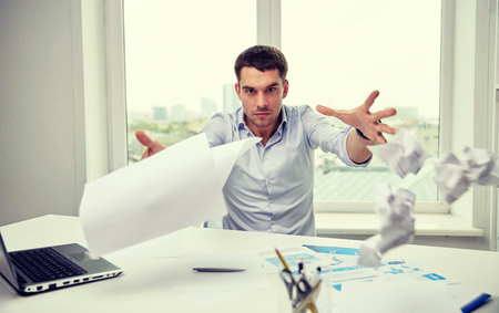 business, people, stress, emotions and fail concept - angry businessman throwing papers in office Stock Photo
