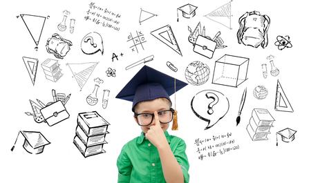 Kindheit, Schule, Bildung, Lernen und Menschen Konzept - glücklicher Junge in Bachelor-Hut oder Doktorhut und Brillen mit Kritzeleien