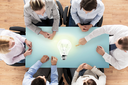 sitting people: business, people and team work concept - close up of creative team sitting at table and pointing finger to lighting bulb in office