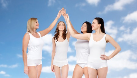 clouds making: gesture, friendship, beauty, body positive and people concept - group of happy different women in white underwear making high five over blue sky and clouds background