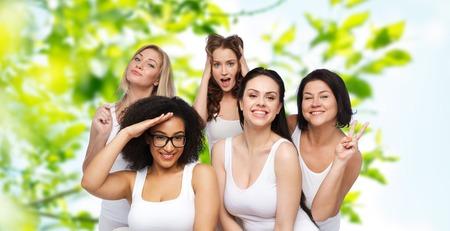 mujeres felices: La amistad, la belleza, el cuerpo positivo y el concepto de la gente - grupo de mujeres felices más tamaño en ropa interior blanca divertirse y hacer caras sobre fondo natural verde Foto de archivo