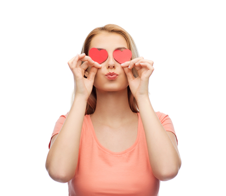 donna innamorata: love, romance, valentines day and people concept - smiling young woman or teenage girl with red heart shapes on eyes