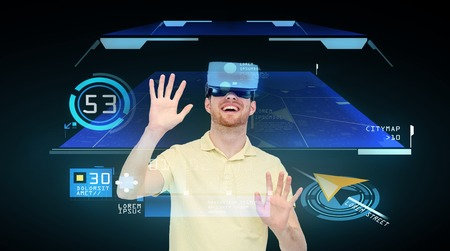 mediated: 3d technology, virtual reality, cyberspace, entertainment and people concept - happy young man with virtual reality headset playing game over gps navigator projection and black background Stock Photo