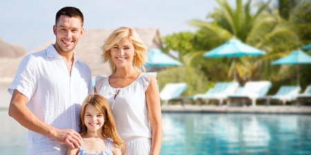 beach holiday: summer holidays, travel, tourism, vacation and people concept - happy family over hotel resort swimming pool and sun beds background Stock Photo