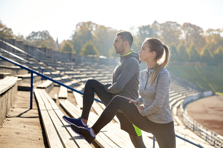 fitness hombres: fitness, sport, exercising and lifestyle concept - couple stretching leg on stands of stadium