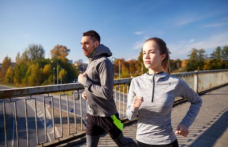 fitness hombres: fitness, deporte, personas y concepto de jogging - feliz pareja ejecutan al aire libre Foto de archivo