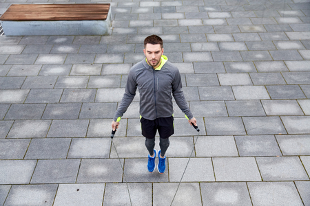 saltar la cuerda: fitness, sport, people, exercising and lifestyle concept - man skipping with jump rope outdoors