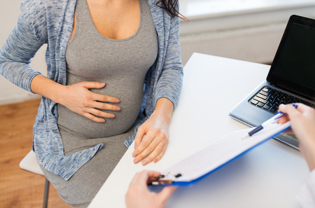 pregnancy, gynecology, medicine, health care and people concept - close up of gynecologist doctor with clipboard and pregnant woman meeting at hospital