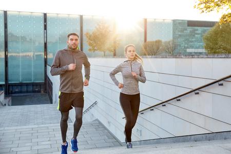 fitness, deporte, la gente, el ejercicio y el concepto de estilo de vida - feliz pareja corriendo arriba en las escaleras de la ciudad