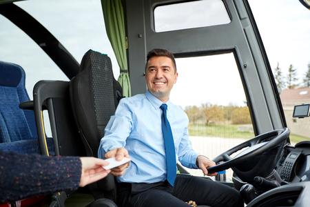 buses: transport, tourism, road trip and people concept - smiling bus driver taking ticket or plastic card from passenger