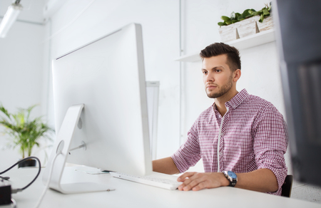 young guy: business, technology, education and people concept - young creative man or student with computer at office Stock Photo