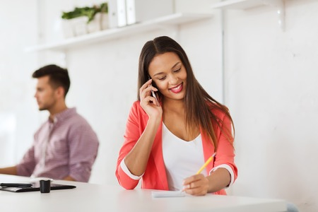 business, startup, communication and people concept - happy african american businesswoman or creative worker calling on smartphone at office