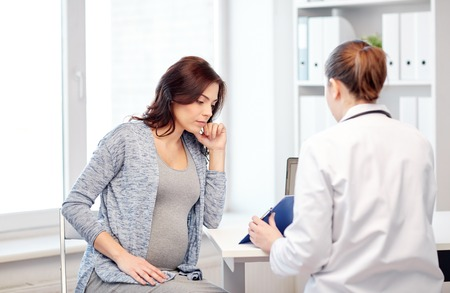 gynecologist: pregnancy, gynecology, medicine, health care and people concept - gynecologist doctor with clipboard and pregnant woman meeting at hospital Stock Photo