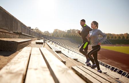 fitness hombres: fitness, deporte, ejercicio y estilo de vida concepto - Pareja feliz corriendo arriba en estadio