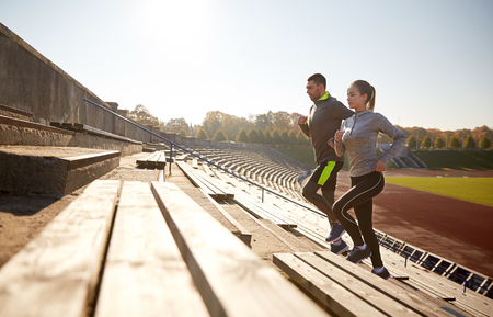 fitness, sport, exercising and lifestyle concept - happy couple running upstairs on stadium Stockfoto