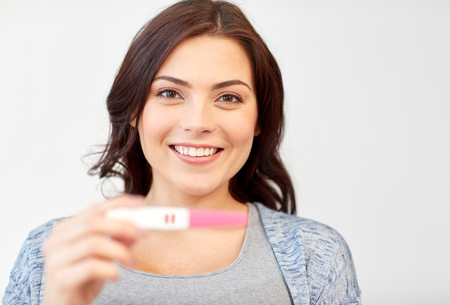 fem: pregnancy, fertility, maternity and people concept - happy smiling woman holding and showing positive home pregnancy test