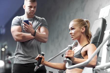 fitness hombres: sport, fitness, bodybuilding, teamwork and people concept - young woman and personal trainer flexing muscles on gym machine Foto de archivo