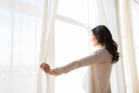 expectation: pregnancy, motherhood, people and expectation concept - close up of happy pregnant woman opening window curtains