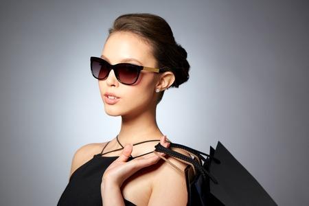 販売、ファッション、人々、高級コンセプト - ショッピング バッグ灰色の背景の上に黒いサングラスで幸せな美しい若い女