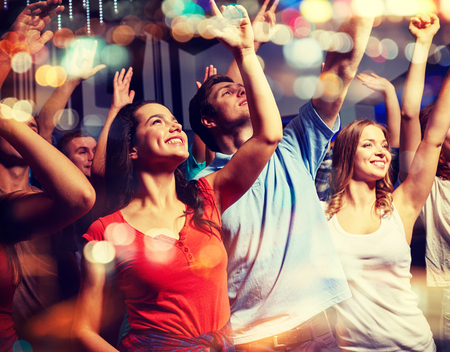 partito, feste, celebrazioni, vita notturna e la gente concept - amici sorridenti che fluttuano le mani al concerto in club di