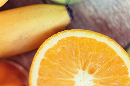 healthy eating, food, fruits and diet concept - close up of fresh juicy cut orange and banana on table