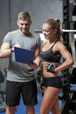 fitness hombres: fitness, deporte, ejercicio y dieta concepto - mujer joven y entrenador personal con el portapapeles escribir plan de ejercicios en el gimnasio sonriendo