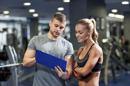 fitness trainer: fitness, sport, exercising and diet concept - smiling young woman and personal trainer with clipboard writing exercise plan in gym