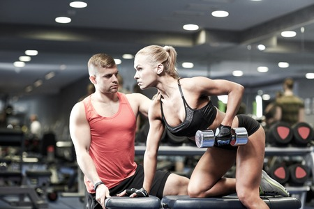 trainers: fitness, sport, exercising, bodybuilding and weightlifting concept - young woman and personal trainer with dumbbells flexing muscles in gym