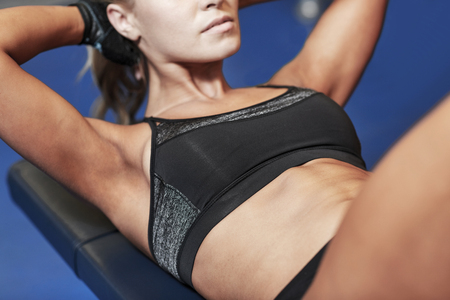 situp: fitness, sport, training and lifestyle concept - close up of woman flexing abdominal muscles on bench in gym