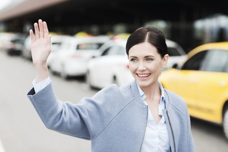 trip over: travel, business trip, people, gesture and tourism concept - smiling young woman over taxi waving hand at airport terminal or railway station