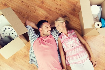 home, people, repair and real estate concept - happy couple with cardboard boxes and stuff lying on floor to new place Stock Photo
