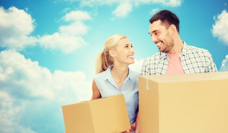 post man: home, people, delivery and real estate concept - happy couple holding cardboard boxes over blue sky and clouds background Stock Photo