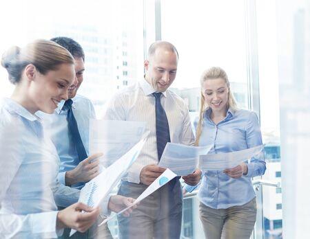 Negocio, trabajo en equipo, la gente y la tecnología concepto - sonriendo equipo de negocios con papeles reunión en la oficina Foto de archivo - 62021999