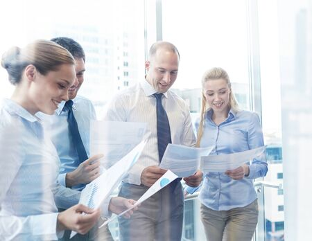 jovenes felices: negocio, trabajo en equipo, la gente y la tecnología concepto - sonriendo equipo de negocios con papeles reunión en la oficina
