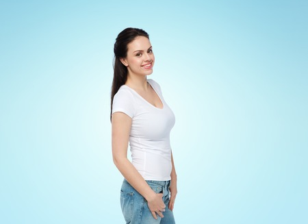 beautiful teen: advertisement, clothing and people concept - happy smiling young woman or teenage girl in white t-shirt over blue background