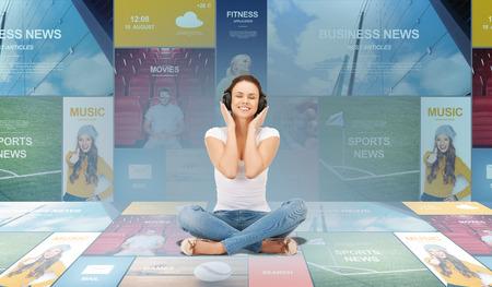tecnologia, musica e il concetto di felicità - sorridente giovane donna o adolescente ragazza in cuffia su schermi virtuali e applicazioni web di sfondo Archivio Fotografico
