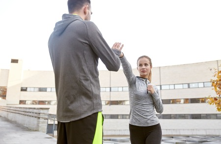 defensa personal: fitness, deporte, la gente, el ejercicio y las artes marciales concepto - mujer joven con el entrenador de la elaboración de auto defensa en huelga de calle de la ciudad Foto de archivo