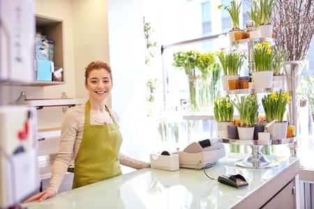 floristry: people, business, sale and floristry and concept - happy smiling florist woman at flower shop counter