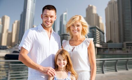 summer holidays, travel, tourism, vacation and people concept - happy family over dubai city street background Stock Photo