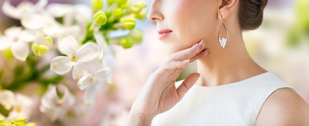 glamour luxury: glamour, beauty, jewelry and luxury concept - close up of beautiful woman face with pearl earring over natural spring lilac blossom background