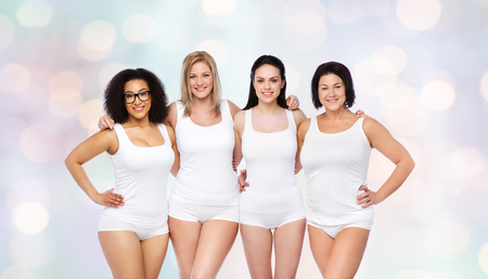 mujeres negras: friendship, beauty, body positive and people concept - group of happy women different in white underwear over holidays lights background