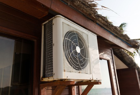 expel: cooling, freshness and heat concept - close up of air conditioner at bungalow house outdoors
