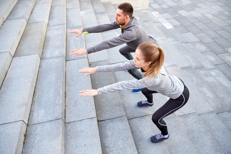 squats: fitness, sport, people, exercising and lifestyle concept - couple doing squats on city street stairs