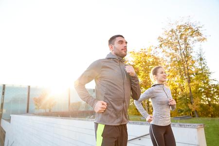 fitness hombres: fitness, deporte, la gente, el ejercicio y el concepto de estilo de vida - feliz pareja corriendo arriba en las escaleras de la ciudad