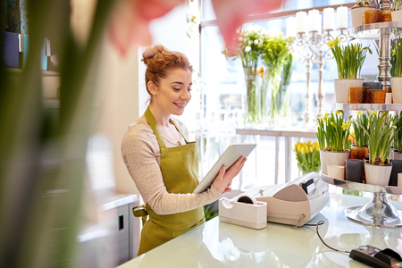 people, business, technology, sale and floristry and concept - happy smiling florist woman with tablet pc computer at flower shop