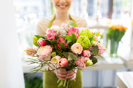 people, business, sale and floristry concept - close up of florist woman holding bunch at flower shop