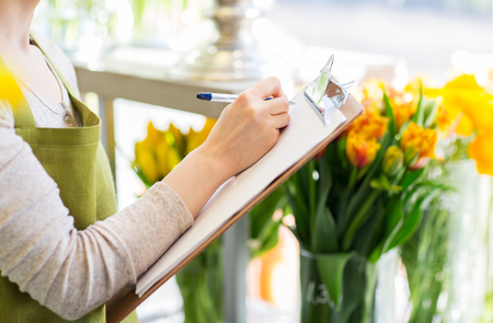 floristry: people, sale, retail, business and floristry concept - close up of happy smiling florist woman with clipboard writing and making notes order at flower shop