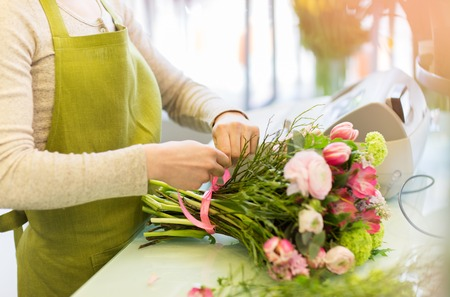 floristry: people, business, sale and floristry concept - close up of florist woman making bunch at flower shop Stock Photo