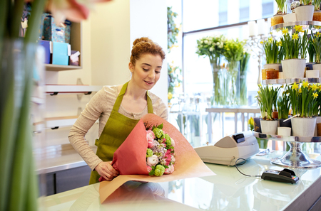 floristry: people, business, sale and floristry concept - happy smiling florist woman wrapping bunch into paper at flower shop Stock Photo