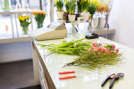 sale shop: people, business, sale and floristry concept - close up of floristic tools on flower shop counter